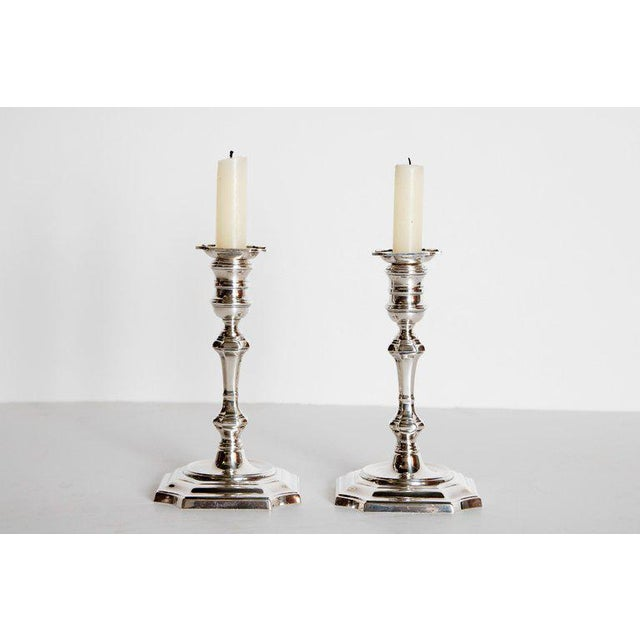 A beautiful pair of George II style candlesticks with octagonal bases with oval borders. The molded stems are topped with...