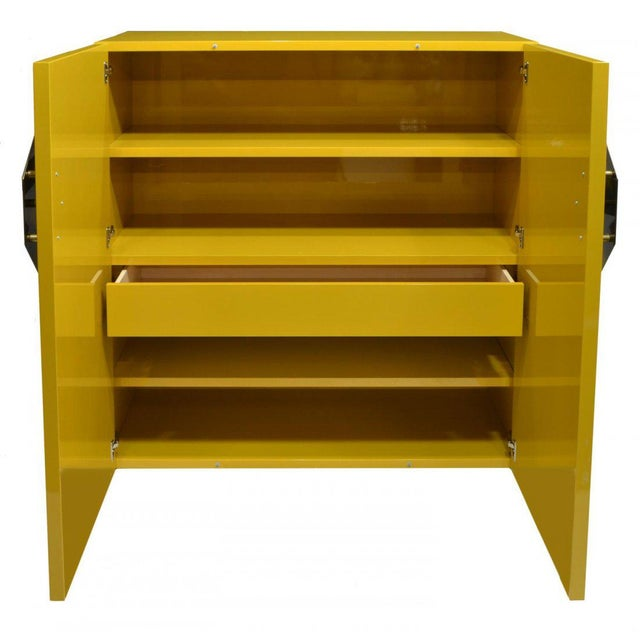 A fantastic Mid-Century Modern yellow high-gloss lacquered cabinet with large brass or steel asterisk pulls. Inside has 4...