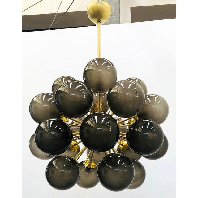 Italian chandelier with frosted smoky Murano glass globes mounted on natural brass frame / Designed by Fabio Bergomi for...