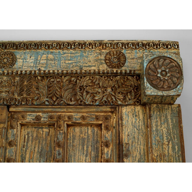 Asian (probably Indian) blue & white distressed painted and carved pair of doors in a frame with a separate pediment...