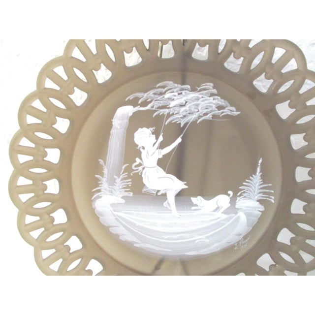 Charming vintage pair of smoke glass display plates each featuring a hand-painted scene of a girl on a swing and a boy...