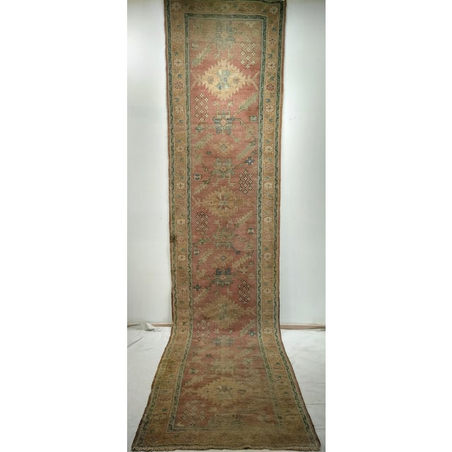 A beautiful light pink forms the field color of this wonderful Turkish Oushak runner from early 1900s. The field has large...