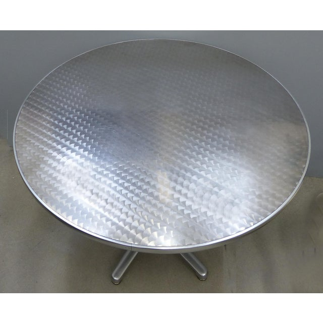 Offered for sale is a polished aluminum round bistro table with a cast aluminum base designed in 1988 by Argentinian...