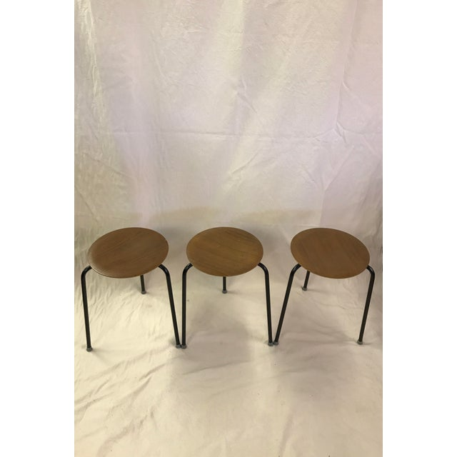 Set of 3 Danish stacking stools in the style of Arne Jacobsen. These bent plywood stools have 3 metal legs each and...