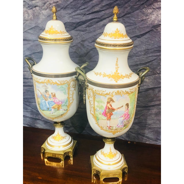 Wonderful pair of hand painted urns. Lion and ring handles at each side. Pedestal base and ornate handles. These vintage...