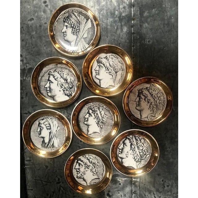 """Set of eight vintage Piero Fornasetti """"Monete"""" little plates, Italy, 1970s. Eight Fornasetti porcelain Monete (Coins)..."""