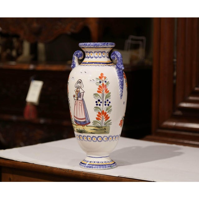 This antique ceramic vase was created in Brittany, circa 1920. Round in shape, the faience piece has curved handles and...