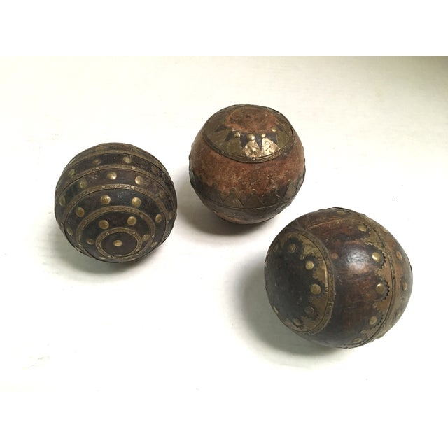 Set of three unique antique solid wood bocce balls. Each one has an individual hammered metal accent design. The balls...