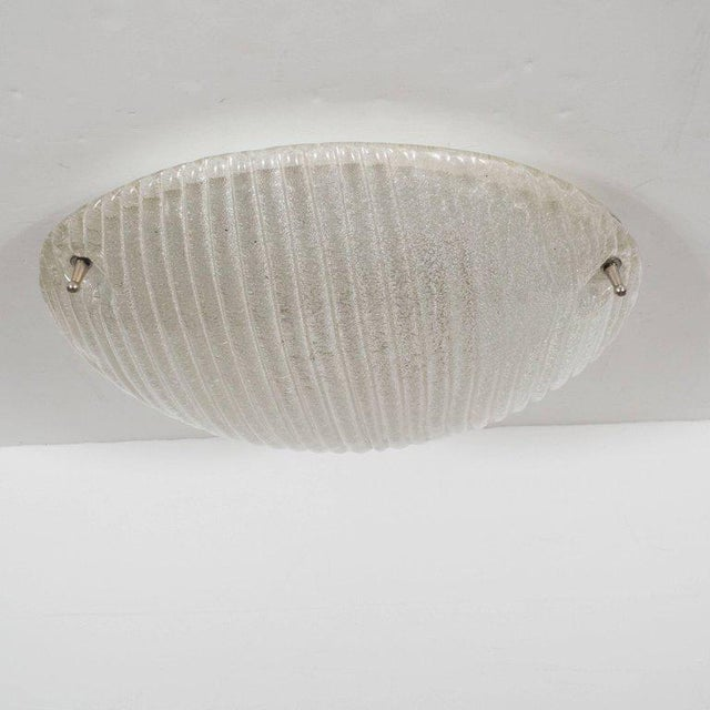 This refined flush mount features a elegant domed form with a multitude of minute bubbles layered into the glass, like the...