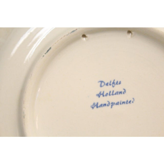 Set of four cobalt blue and antique white Delft hand floral bird scenes painted plates from Holland.