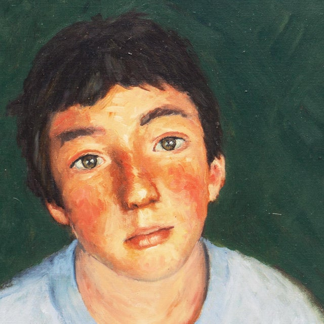 American School portrait of a boy in a soft blue shirt contrasted against a dark green background gazing candidly at the...
