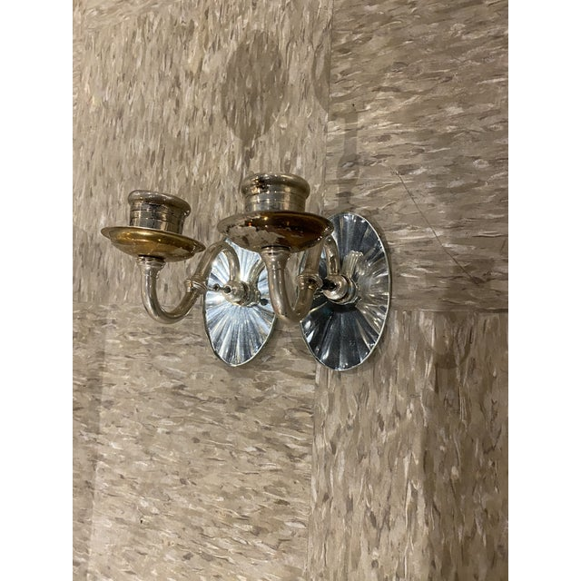 A large set of silver plated one light sconces with mirrored backplate