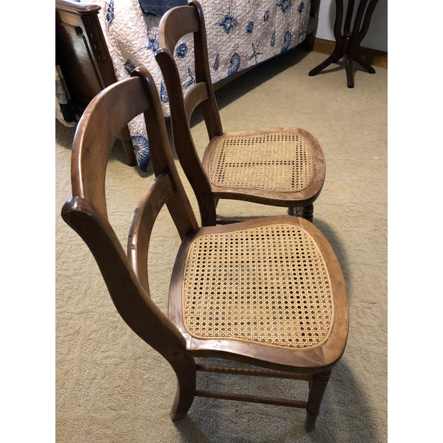 Set of 2 side chairs with slat bowed backs and carved double spindle splaying at front. Sides and back double spindle...