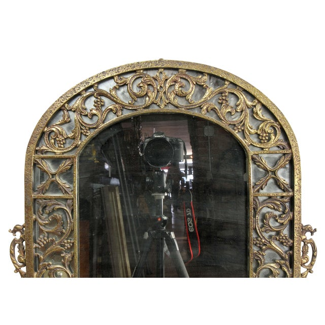 Unsigned with arched top with outer mirror frame with trailing leaf decoration surrounding a conforming mirror plate.