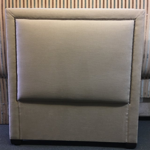 Design Plus Gallery has a new upholstered head board. The piece is upholstered in a Beige Linen with Bronze finish nail...