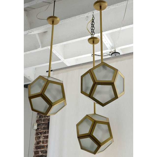 Large cluster chandelier of three pentagon lanterns by Design Frères. Rods can be adjusted at different lengths to create...