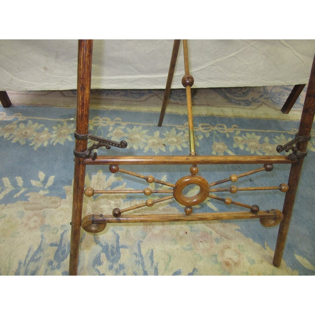 Nice antique oak easel with brass accents. Has hooks near the base where art can be displayed.