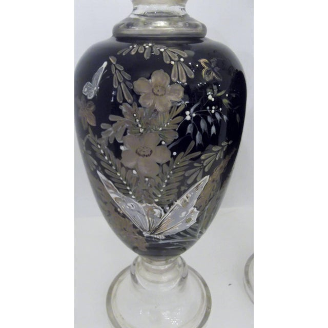 A pair of handblown and hand-painted enamel vases with gilt accents. Clear glass petal tops and pedestal bases. The main...