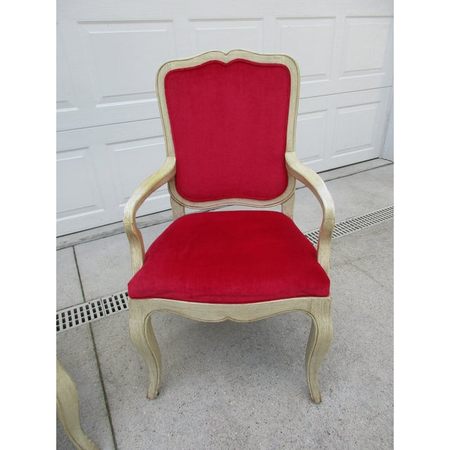 A classic side chair from Baker Furniture with a distressed antique white finish and red velvet upholstery. The chair is...