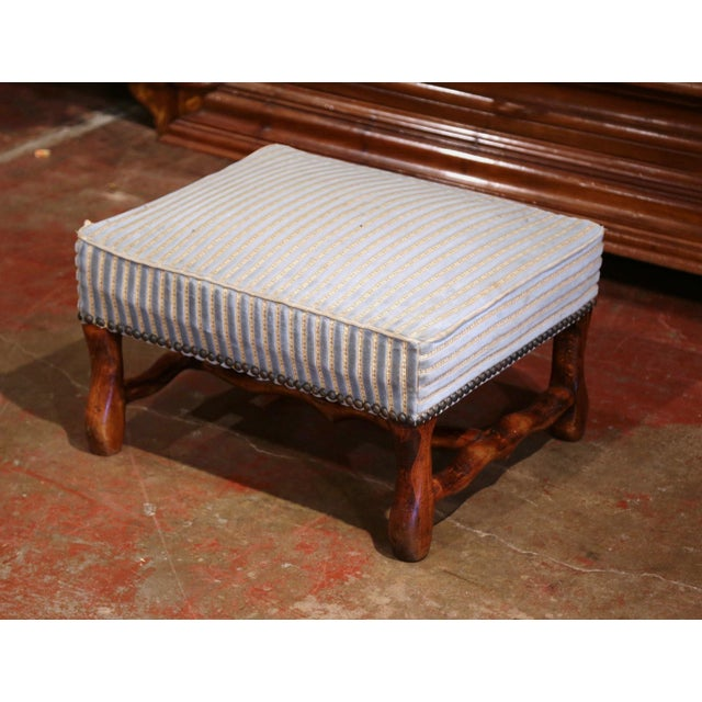 """This elegant, antique ottoman was crafted in Southern France, circa 1920. The large foot stool features four carved """"os de..."""