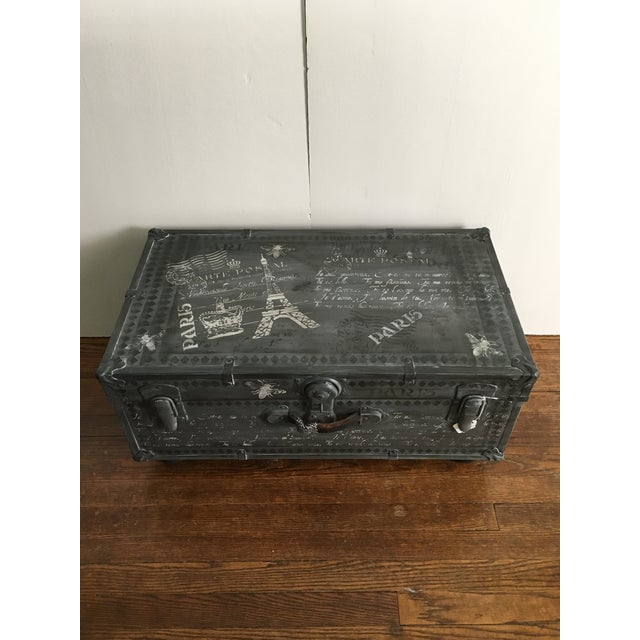 Vintage metal trunk reimagined into a fun coffee table. Painted and distressed in shades of deep grey and white with black...