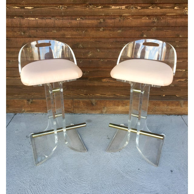 Fantastic pair of lucite and brass bar stools with pale pink upholstery by Hill Manufacturing from the 1970s. These stools...