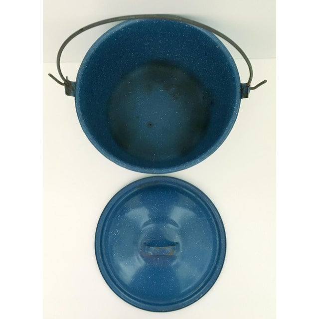 Vintage blue speckled enamelware pot with metal handle. Exterior of pot shows use and has some chipping, interior has...