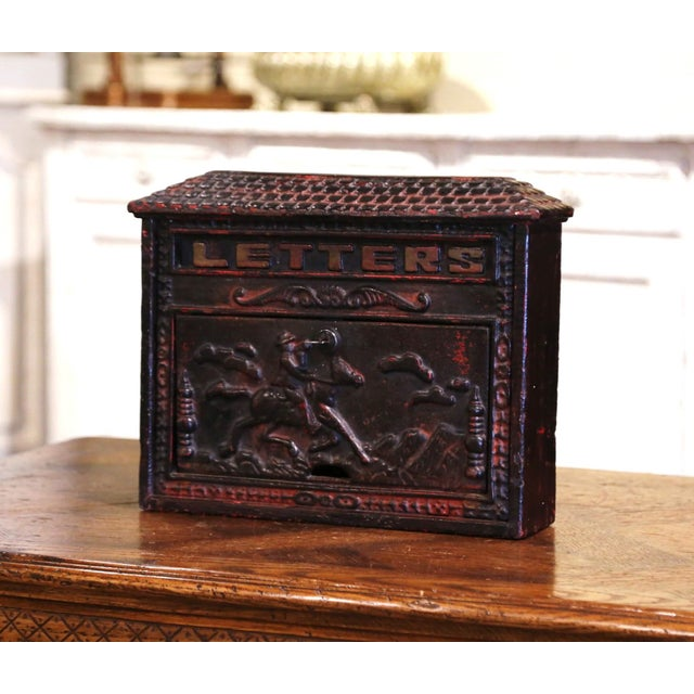 This antique iron mailbox was forged in England, circa 1880. The wall mail holder features high reliefs decorations on the...