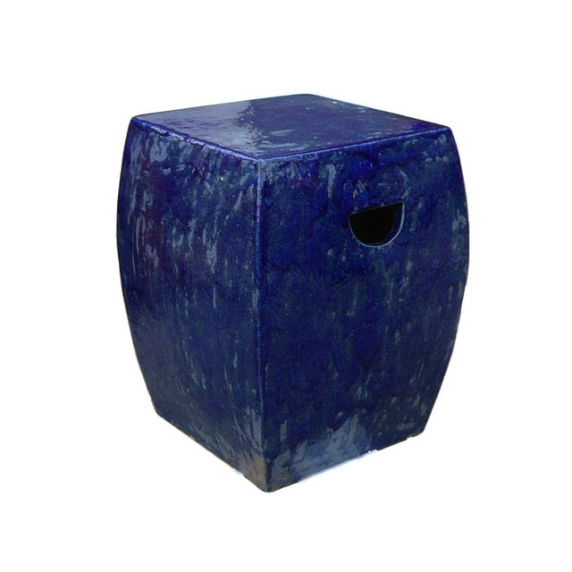 This is a hand made garden clay stool in square shape with plain flat body. The surface is glazed with uneven navy blue...