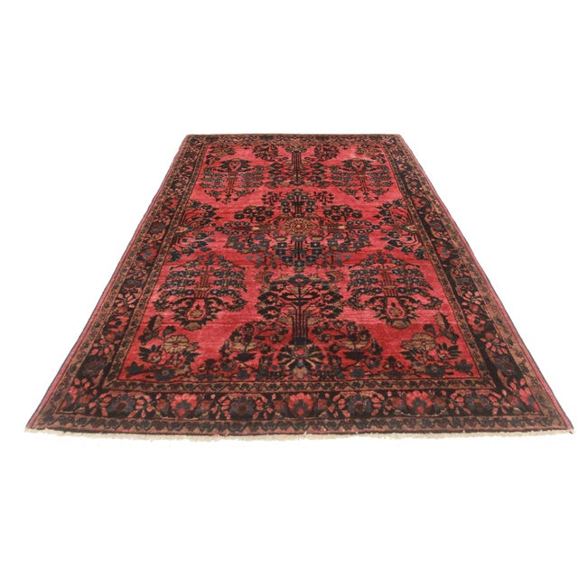 This antique Persian Sarouk rug is comprised of hand-knotted wool. Its all-over design is luxurious and ornate.