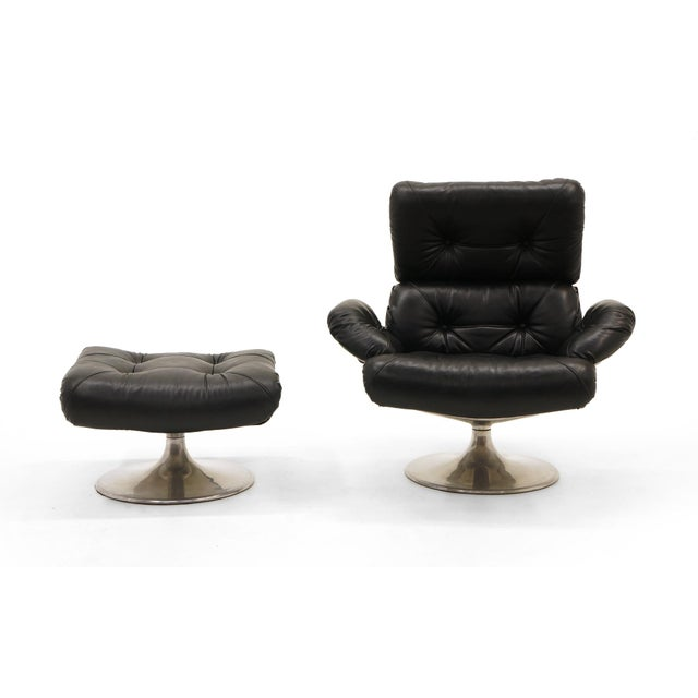 Rare and fine swivel lounge chair and swivel ottoman with cast aluminum and steel frame with original black vinyl...