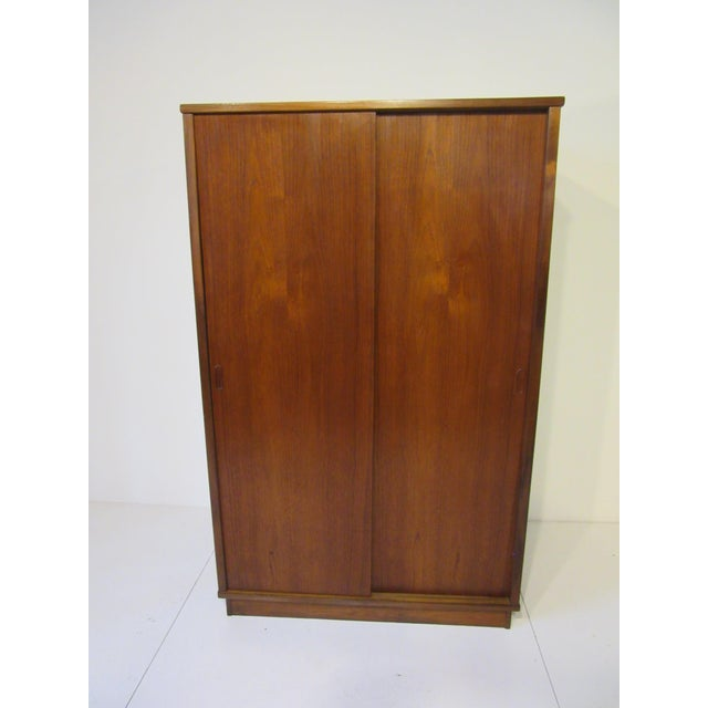 A two sliding door wardrobe with one side having a hanging bar , the other side three adjustable shelves , three drawers...