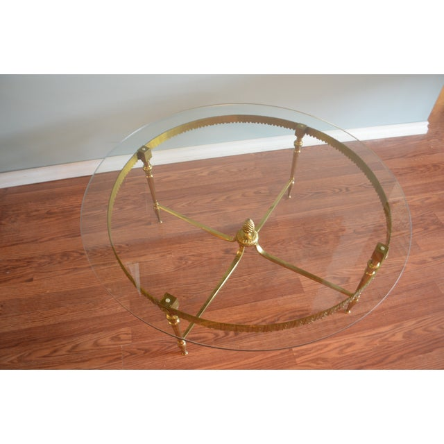 Unusual round coffee table, the brass frame has decorative detail elements all around the apron. The cross bar base has an...