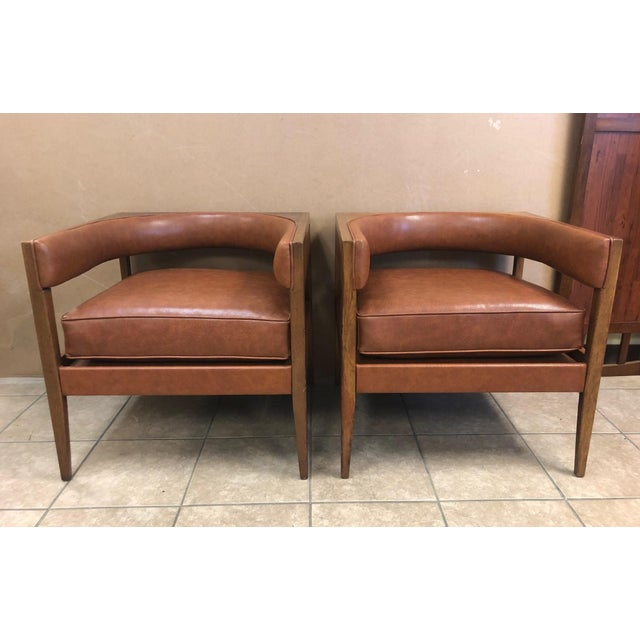 Pair Mid Century Modern Walnut Lounge Chairs. Uniquely shaped with leatherette upholstery.