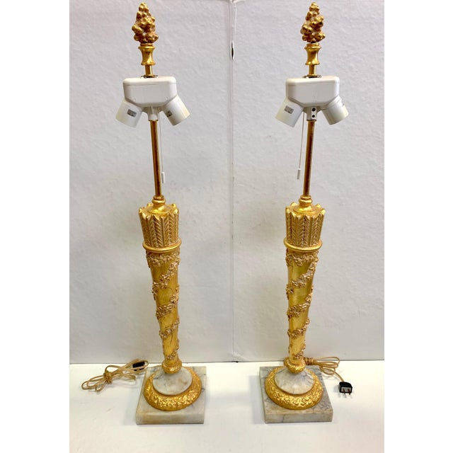 A pair of gold dore table lamps with beautiful marble base. Double light-sockets for extra brightness. Gold dore finials.