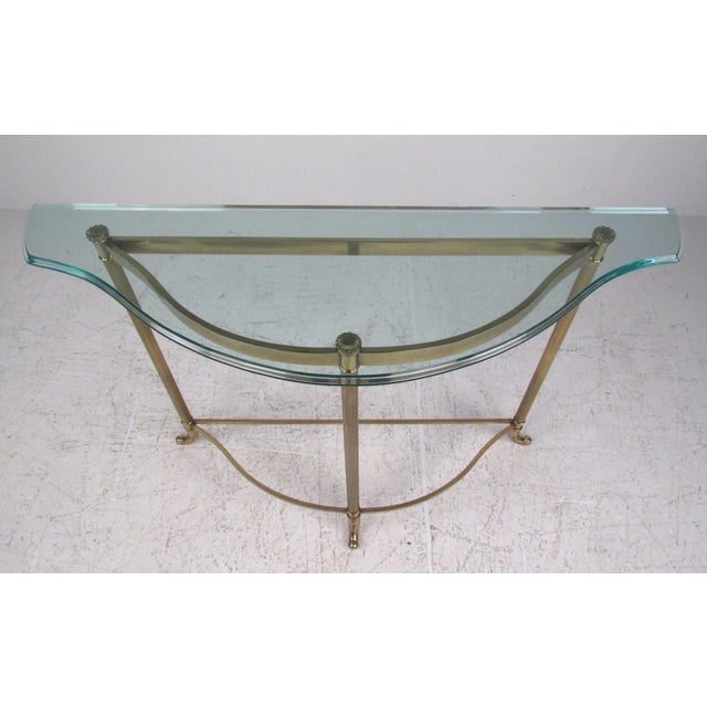 This contemporary modern brass finish demi-lune table features unique feet with a thick glass top. A sleek design with an...