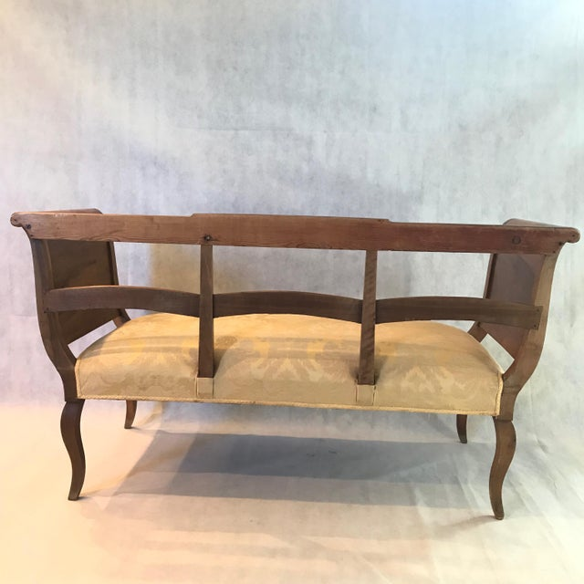 A fine walnut sleigh style settee or sofa having lovely curves, cabrioile legs, and elegant satiny golden jacard upholstery.