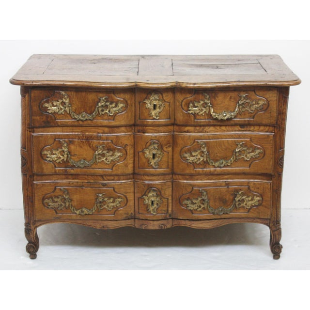 A Louis XV period burled elm ormolu mounted commode.