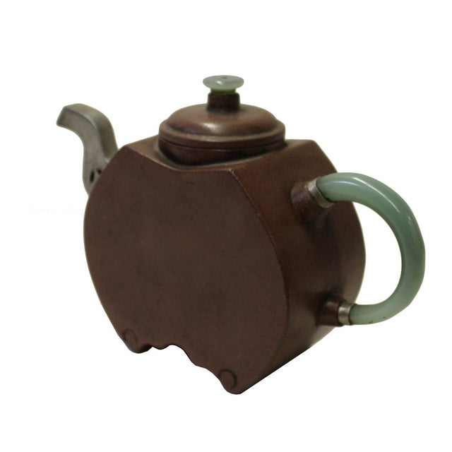 This is a Zisha teapot with clean plain surface and jade stone material handle and pewter metal mouth. Not for beverage...