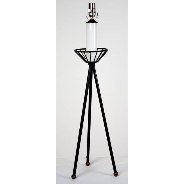 An iron table lamp in the form of a tripod with a modernist iron bobeche. Legs end in brass balls that have their original...