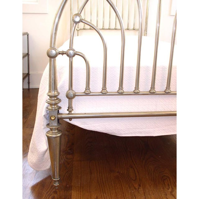An Art Deco period nickel clad headboard and foot-board for a twin size bed with brass bed bolts. Later metal bed rails...