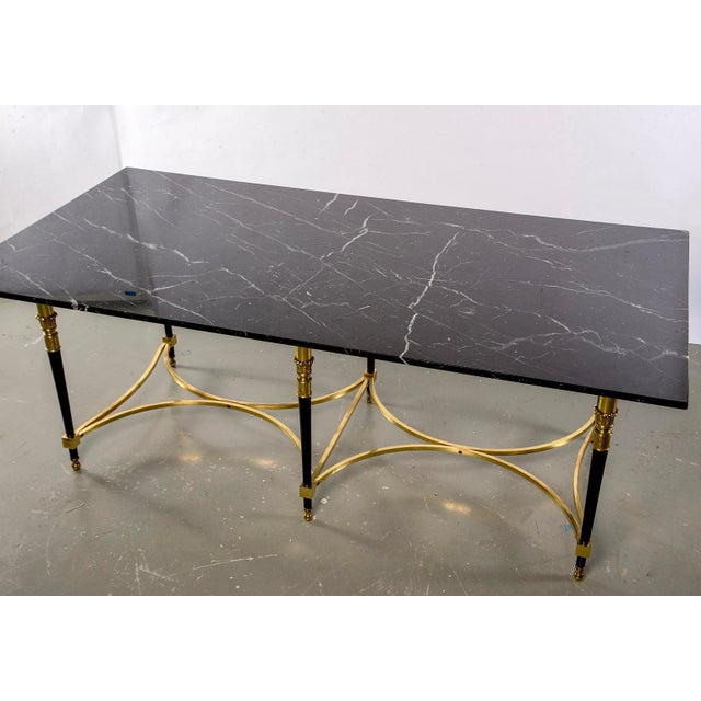 Italian Directoire style centre table has brass stretchers and six brass and black enameled legs, circa 1940s. Top is...