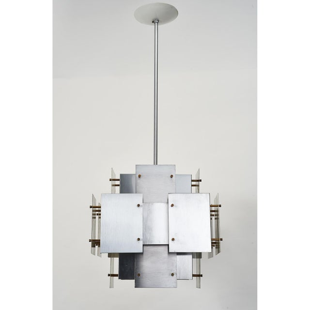 An architectural rectangular chandelier consisting of a three dimensional composition of 'floating' satin steel panels...