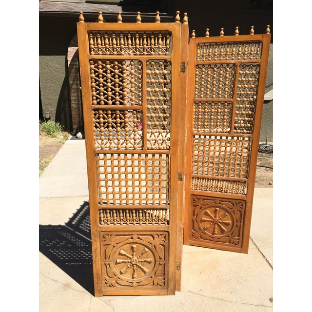 This is an unusual vintage folding screen, with carved wood panels. There is a split in the wood in the central panel, and...