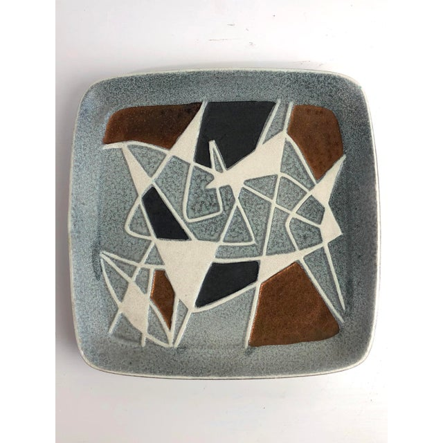A highly collectible modernist art pottery plate/platter. Famously built up from different colors and molded geometric...