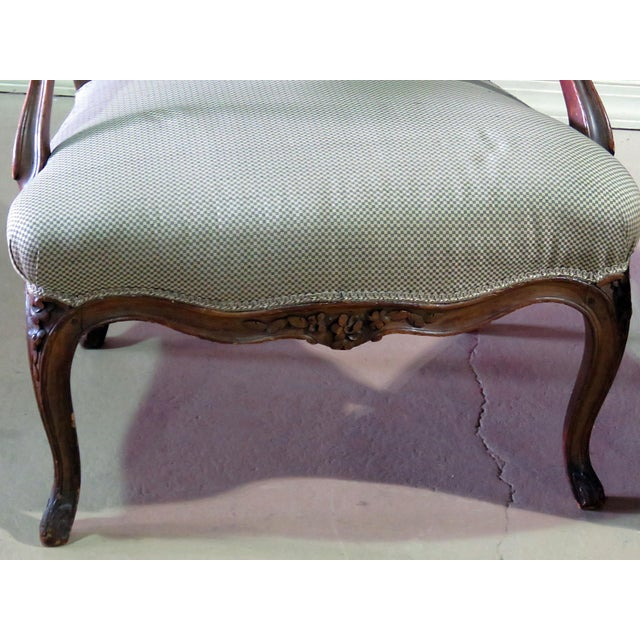 Pair of Louis XV style carved fauteuils with down swept arms and cabriolet legs.