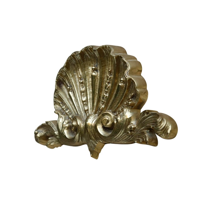 A rococo style brass appliqué. Pressed with a rich fan shaped scallop shell above scrolling acanthus.