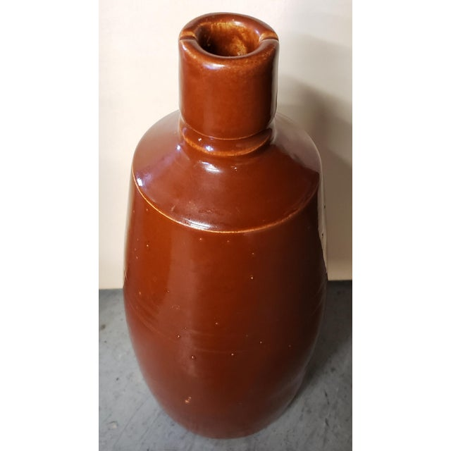 """Up for sale is a Mid 20th Century Reddish Brown Glazed Stoneware Bottle! It measures 8 7/8"""" tall. The piece is in..."""