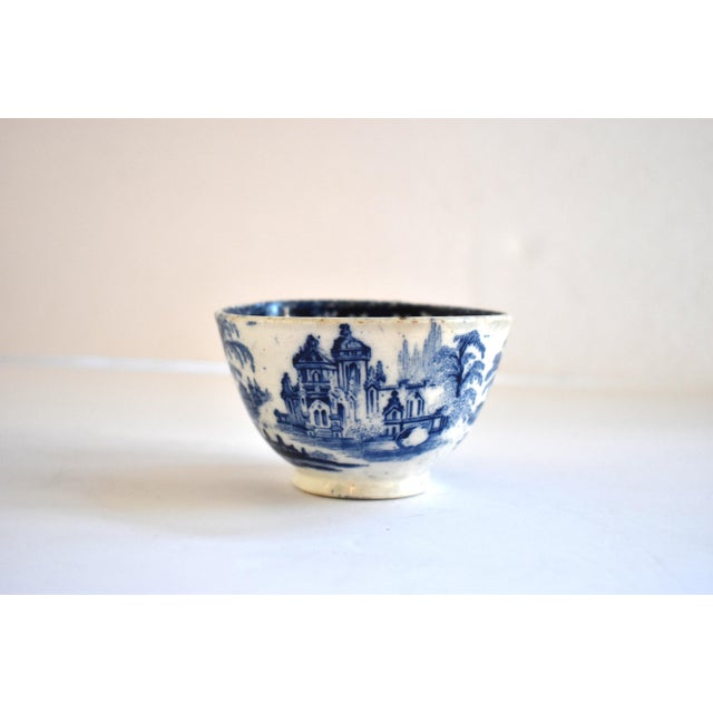 An antique, c. 1810-1820s Staffordshire blue transferware tea bowl , with flowers in the center and castle landscapes...