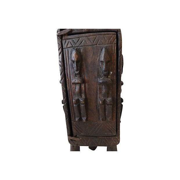 Carved wood standing box with one door used by the Dogon people to store tobacco leaves. The sculptures on the top and the...